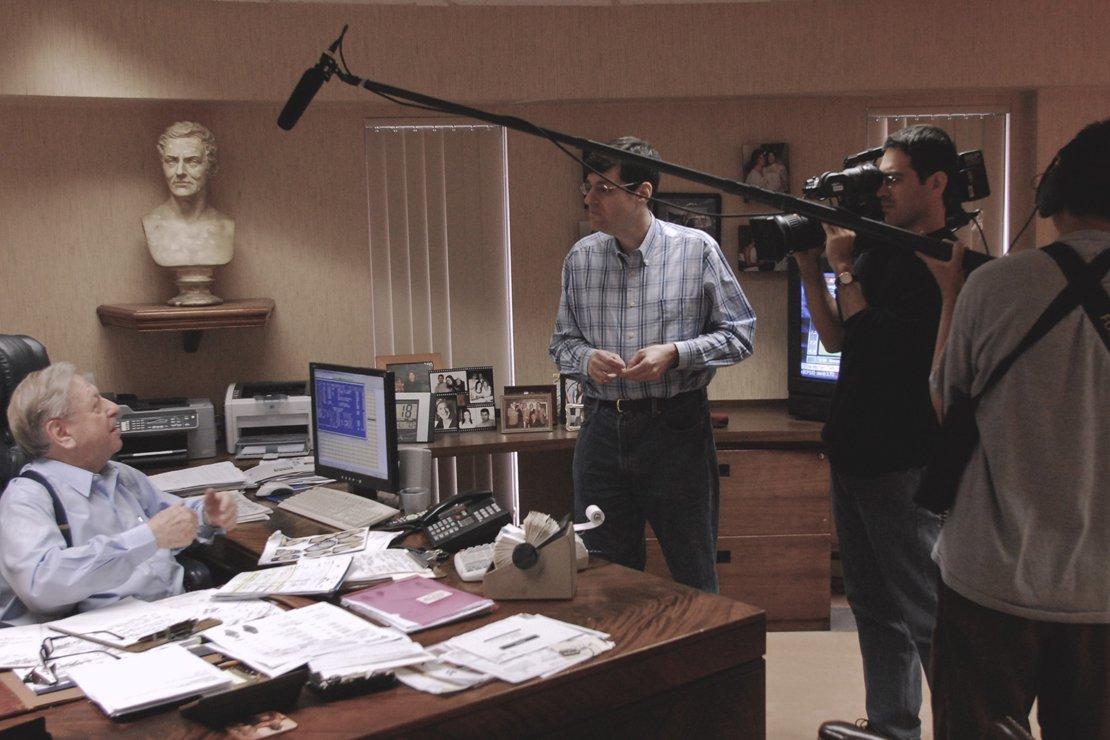 Buddy interviews his father, Mort Clayman, at Jules Jurgenson Corporation.